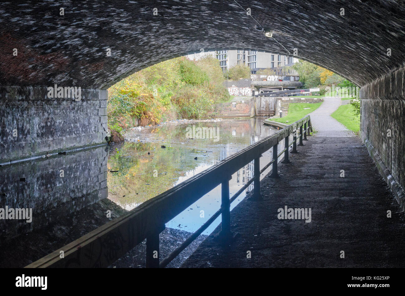 Old brick bridge over the Digbeth Branch Canal and towpath by Birmingham City Universtity in Curzon Street, Birmingham - Stock Image