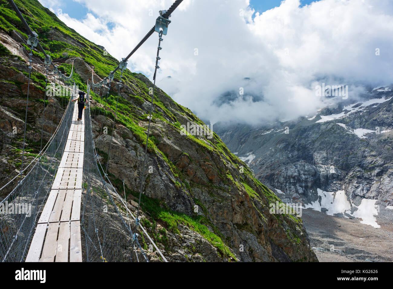 Hiker on a suspension bridge, Chamonix, Rhone Alpes, Haute Savoie, France, Europe Stock Photo