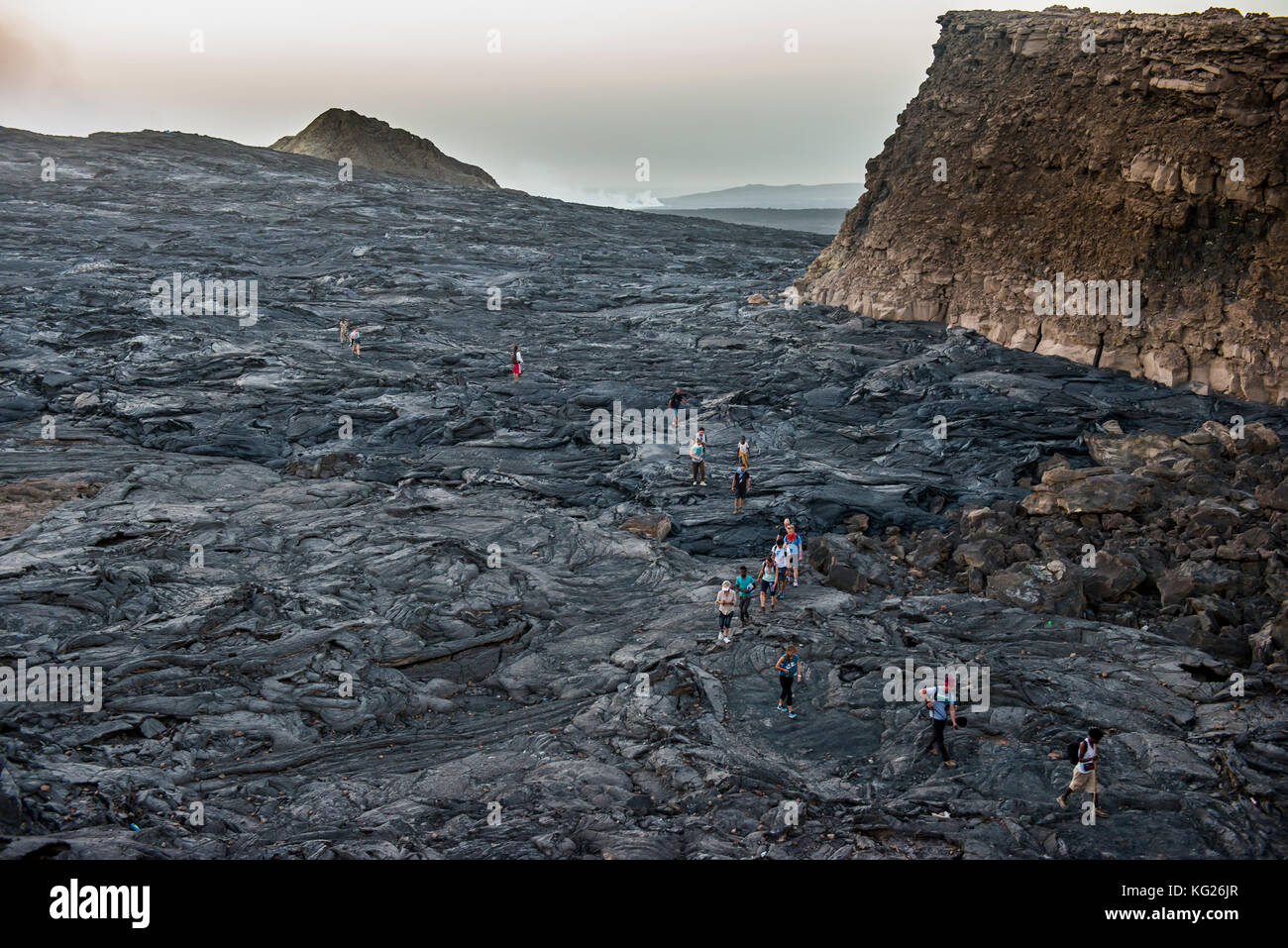 Tourists walking through lava field around the very active Erta Ale shield volcano, Danakil depression, Ethiopia, - Stock Image