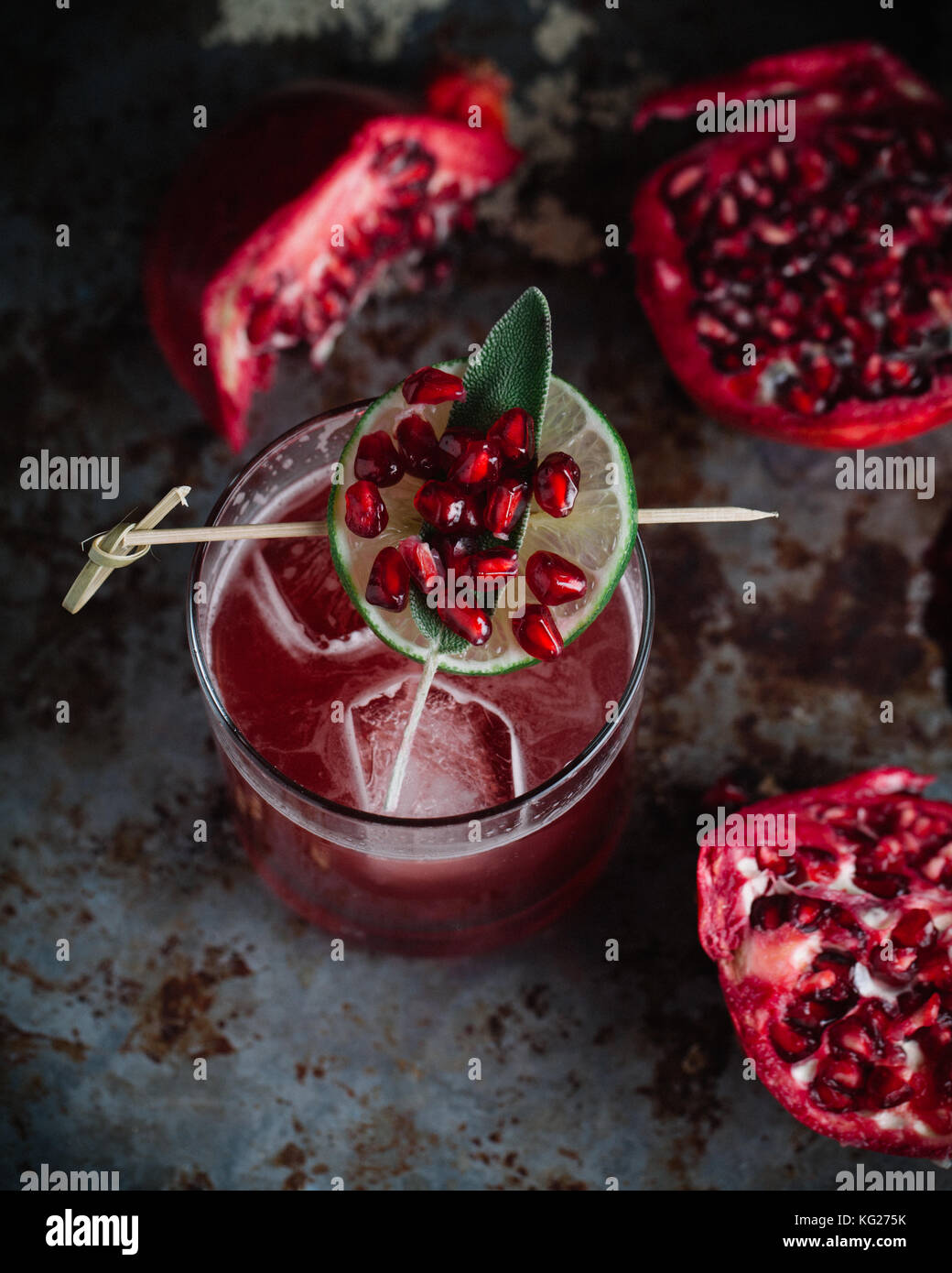 Alcoholic cocktail garnished with pomegranate seeds on dark moody background - Stock Image