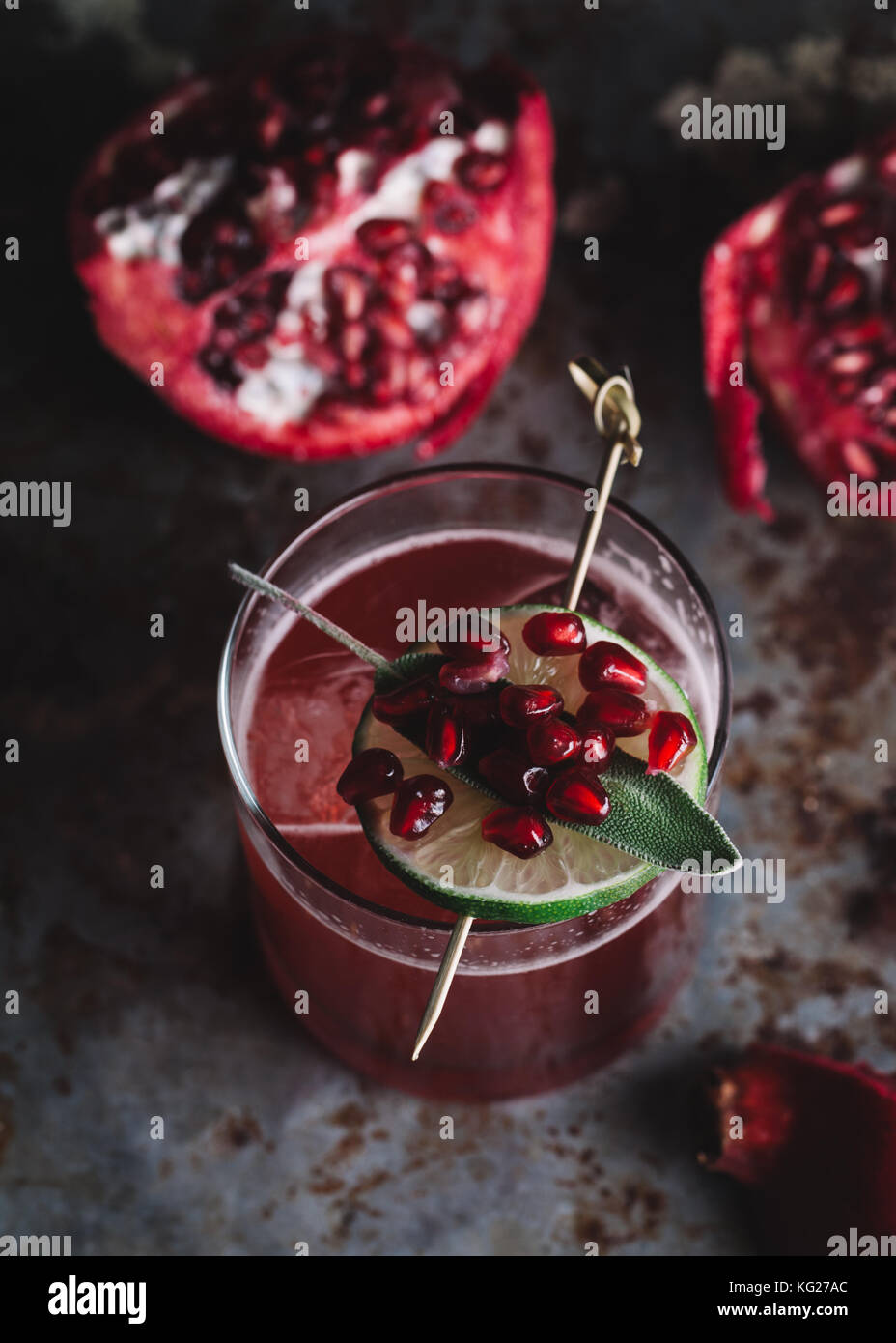 Alcoholic cocktail garnished with pomegranate seeds on dark moody background Stock Photo