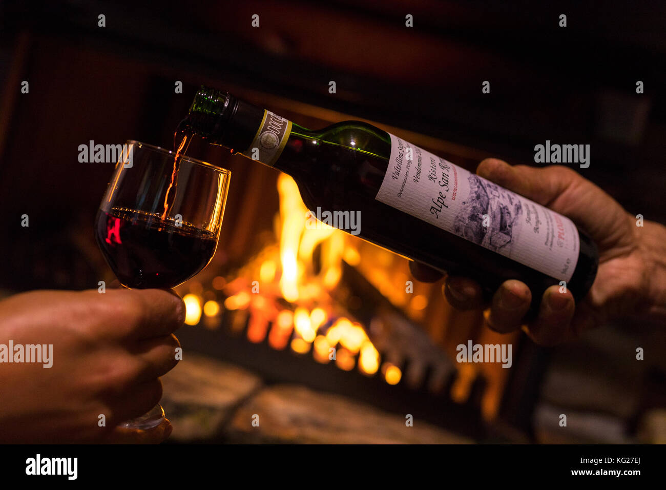 Bottle and glass of wine in front of fireplace, San Romerio Alp, Brusio, Poschiavo Valley, Canton of Graubunden, - Stock Image
