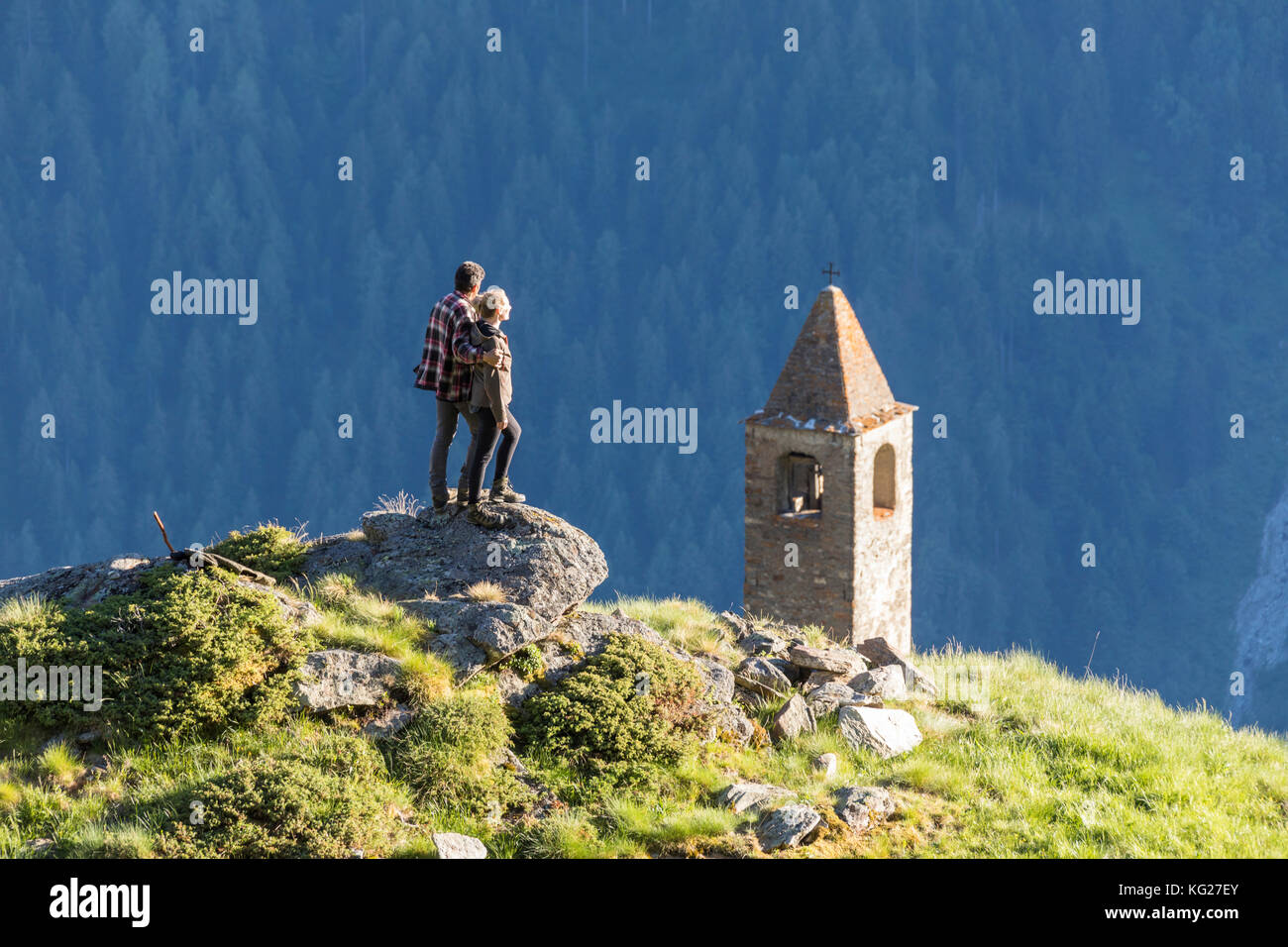 Man and woman embraced look at the bell tower, San Romerio Alp, Brusio, Poschiavo Valley, Canton of Graubunden, - Stock Image