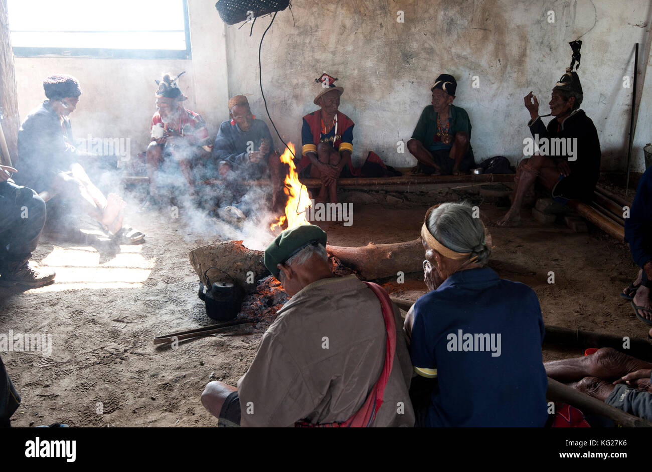 Naga men sitting chatting around the central fire in their village murung (village hall), Hongphui village, Nagaland, - Stock Image