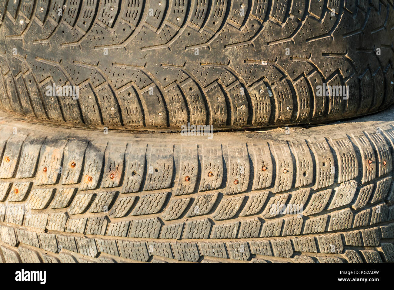 A stack of old tires with textured tread on sunlight closeup - Stock Image