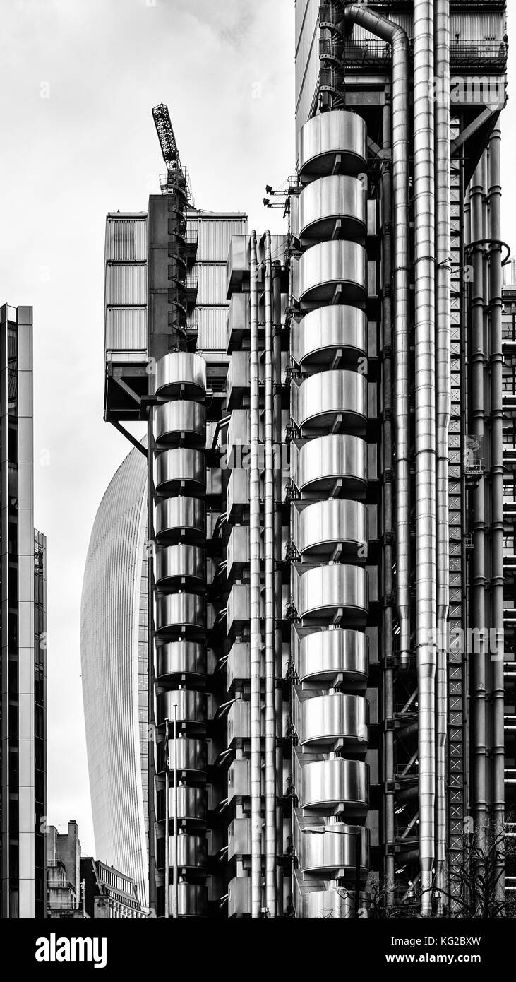 A view past the Lloyds Insurance building to 20 Fenchurch St, City of London, black and white, stainless steel building - Stock Image