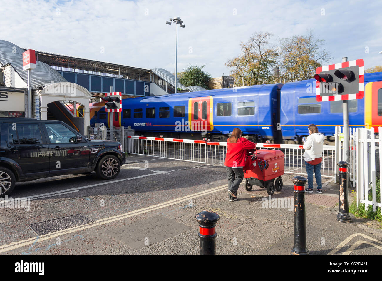 Railway crossing barriers working at Mortlake Train Station, Mortlake, London Borough of Richmond upon Thames, Greater - Stock Image