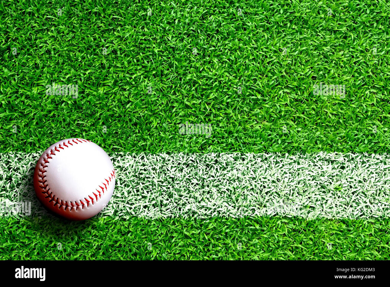 Baseball on field with white line marking and copy space. Line represents infield line or foul line. - Stock Image