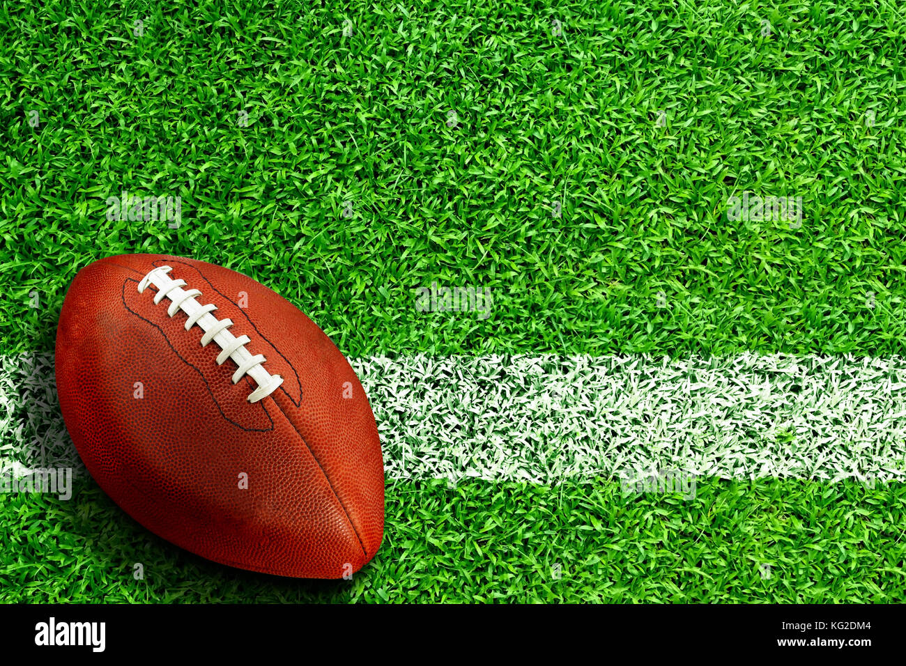 Football on field with white line marking and copy space. Line represents goal line in the end zone, inbound line - Stock Image