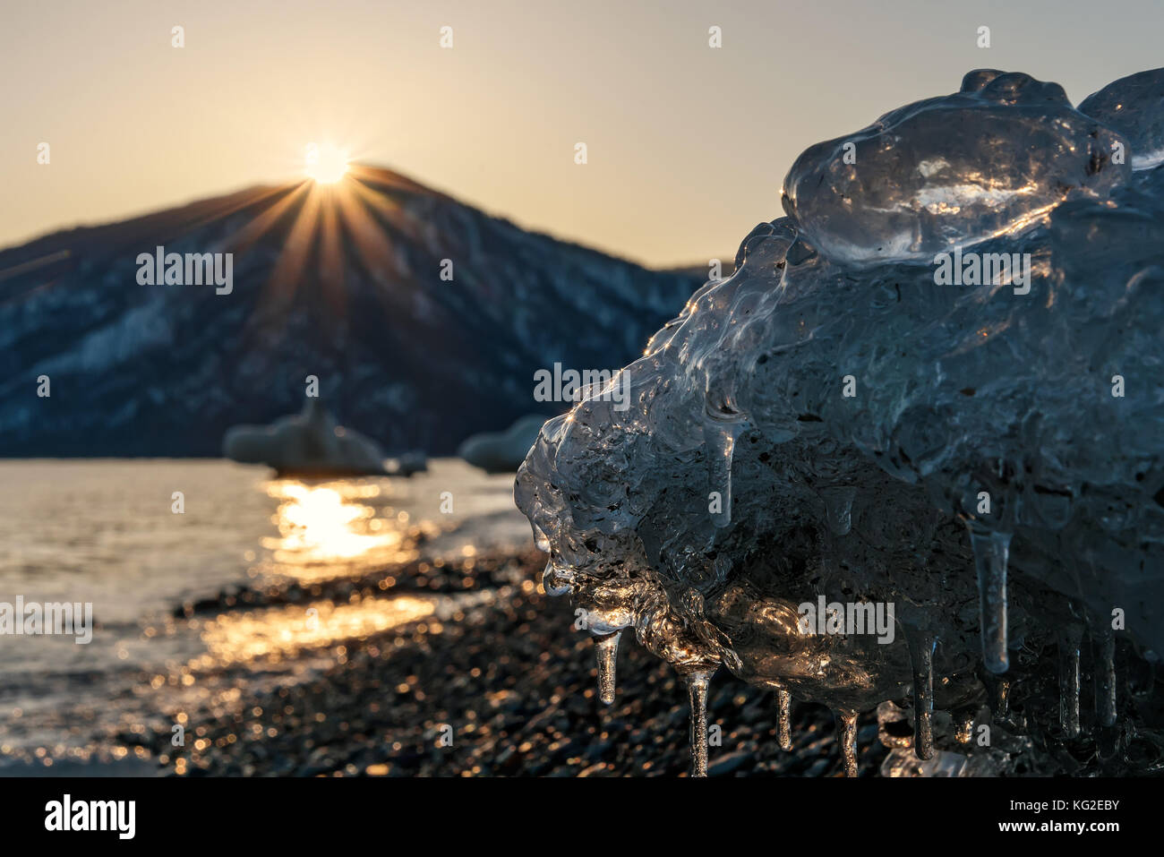Colorful winter view of the sea, the mountains, the sun, the ice on the shore and the sun glare on the water at - Stock Image
