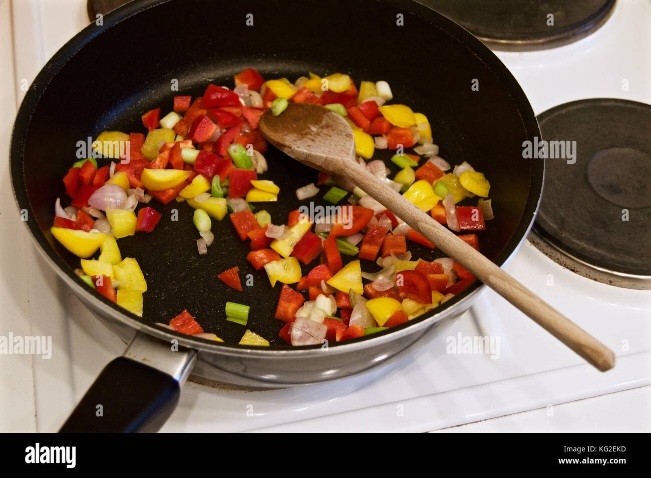 Cooking a paella on the hob in a teflon coated wok with wooden spoon - Stock Image