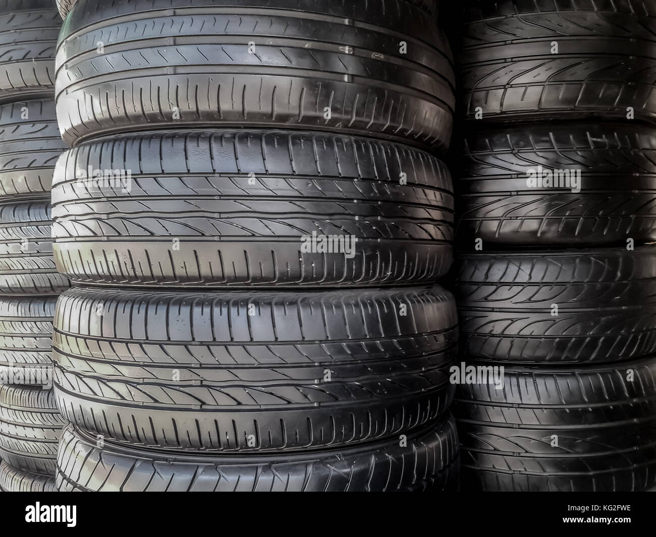 shiny black recapped car tires stack. they are inspected and repair and good to be used in lower cost than new tires. - Stock Image