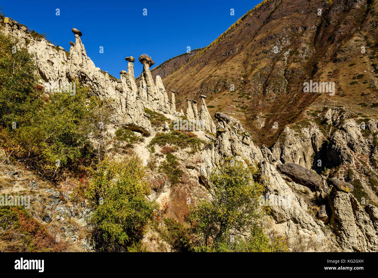 Scenic autumn view with high rocks in the form of stone mushrooms on a background of mountains and blue sky - Stock Image
