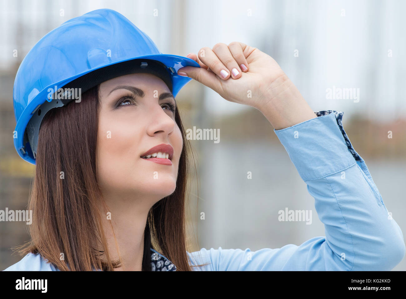 Beautiful woman architect wearing helmet at construction site - Stock Image