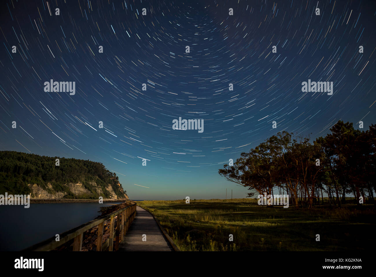 Star trails over a river with a path and a forest Stock Photo