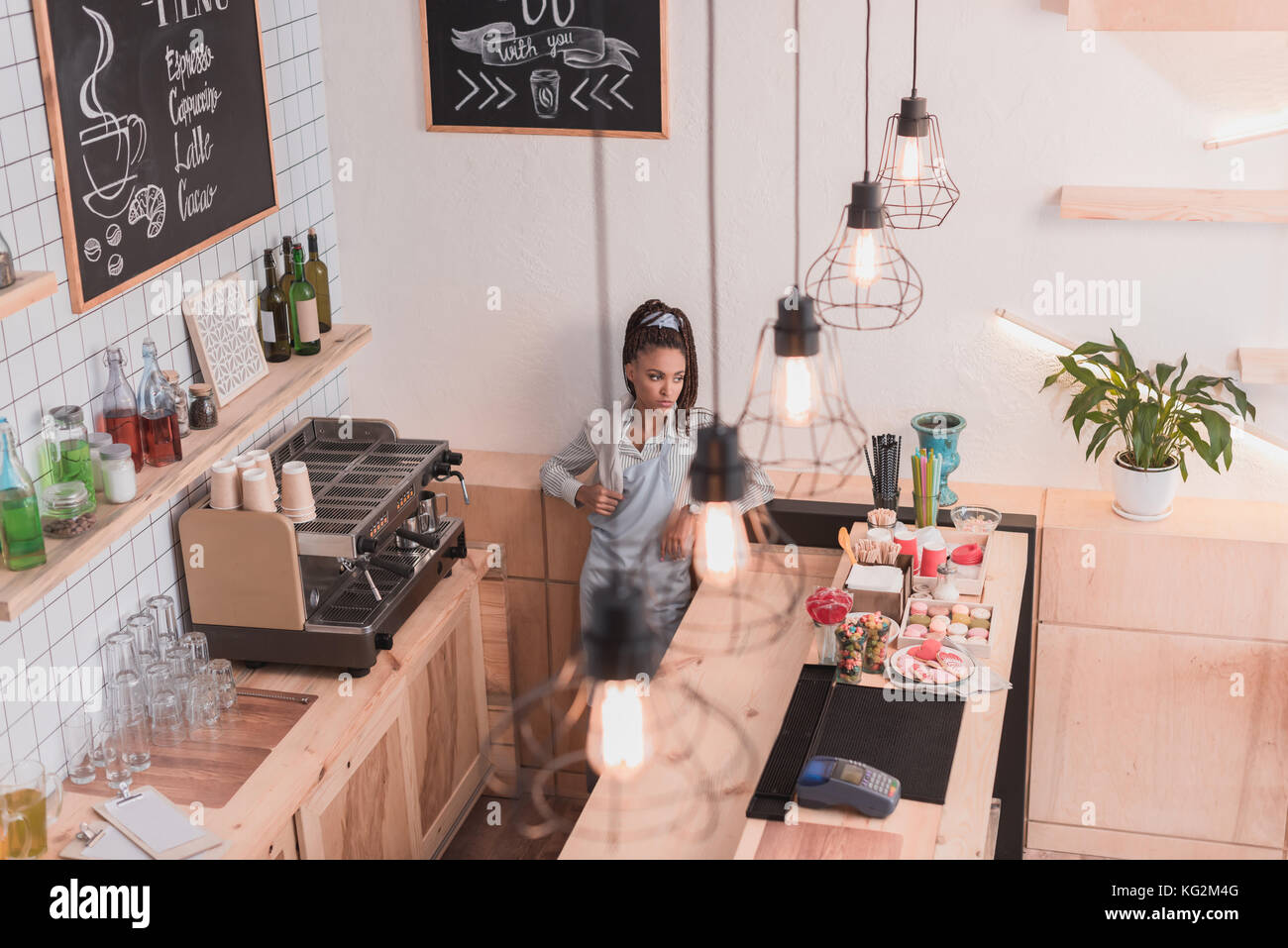 barista standing behind counter - Stock Image