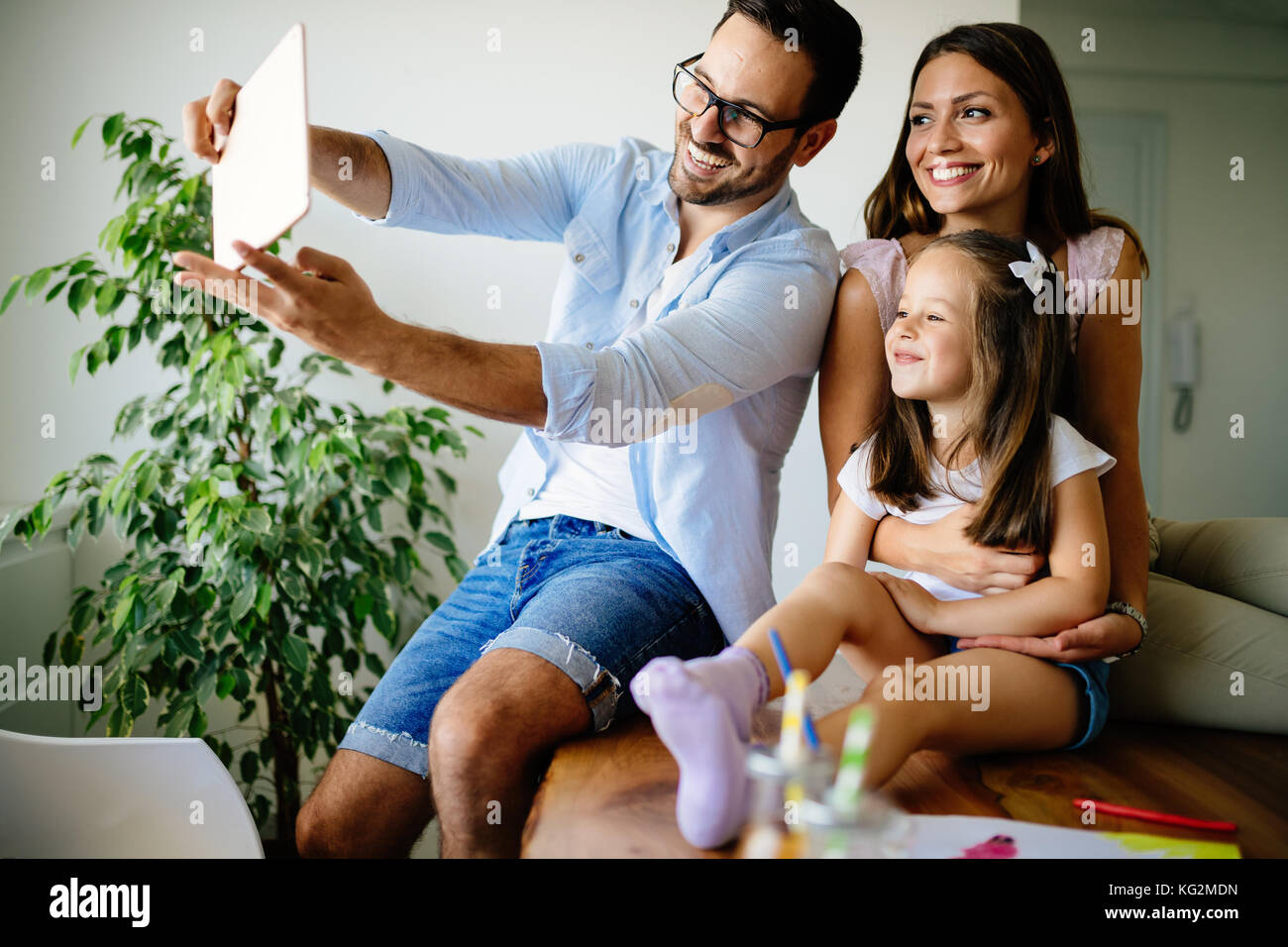 Happy family taking selfie in their house - Stock Image