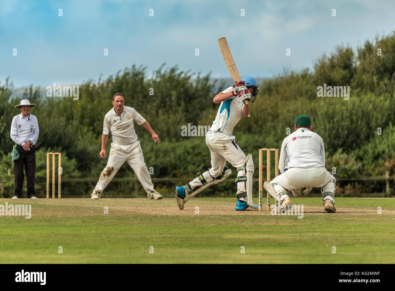 A batsman plays a shot during a Sunday League match between two local Cricket teams. - Stock Image