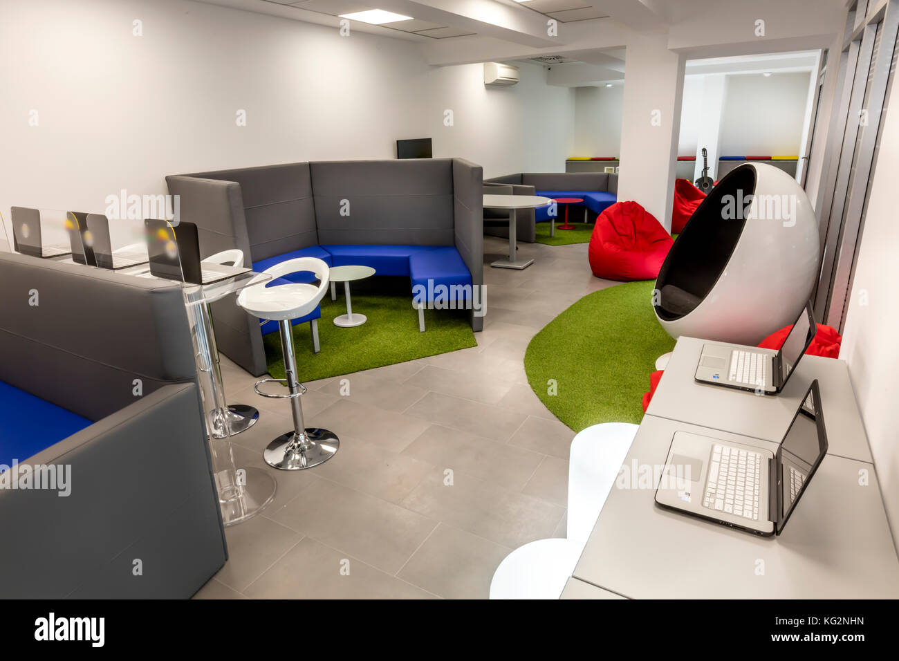 Modern Office Space With Desks And Laptops; Lounge Space In The Background.