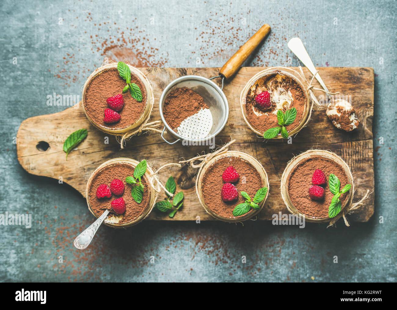 Homemade dessert Tiramisu in glasses on wooden board - Stock Image