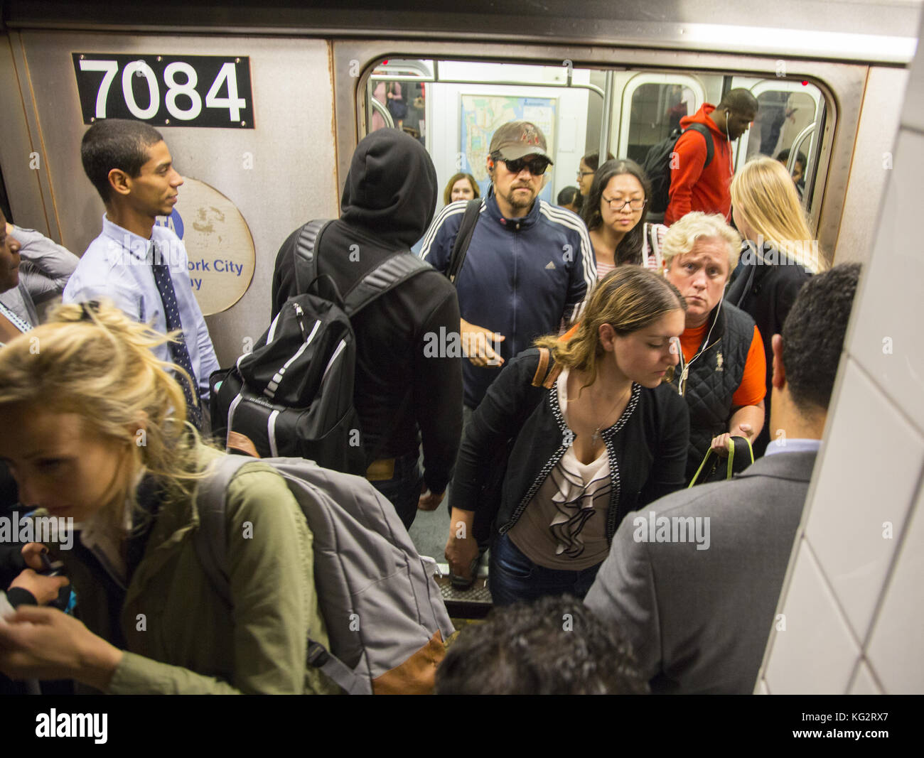 People exit a No. 6 subway train at 59th Street along Lexington Avenue in Manhattan. - Stock Image