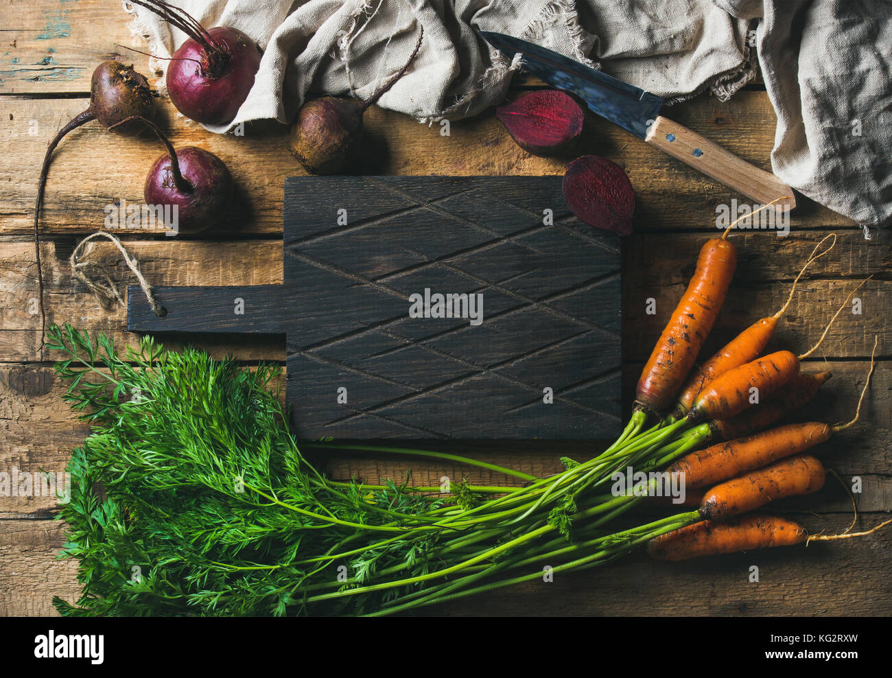 Garden carrots and beetroots with dark cutting board in center - Stock Image
