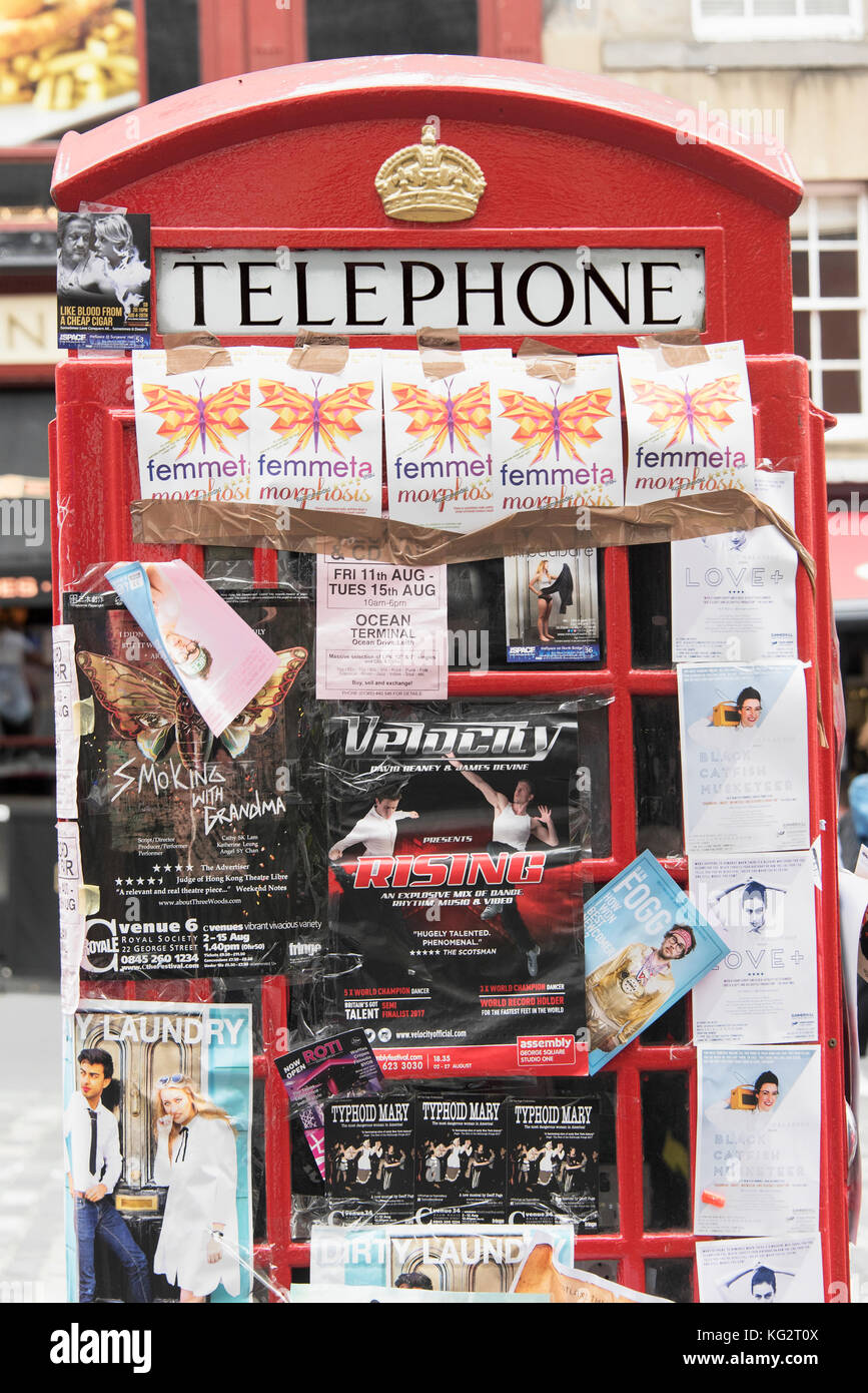 A red telephone box on the Royal MIle in Edinburgh covered in flyers  promoting Festival Fringe shows. - Stock Image