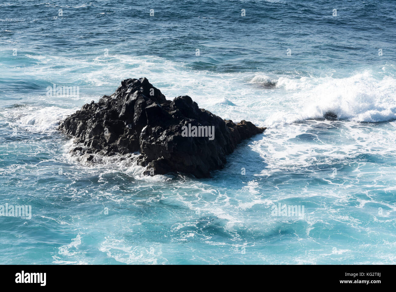 rocks with splashing waves near El Golfo in Lanzarote, Spain Stock Photo