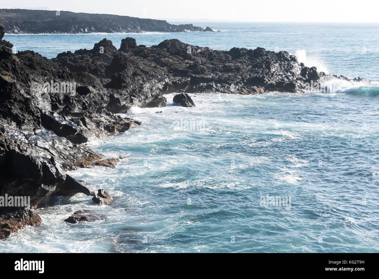 rocks with splashing waves near El Golfo in Lanzarote, Spain Stock Photo