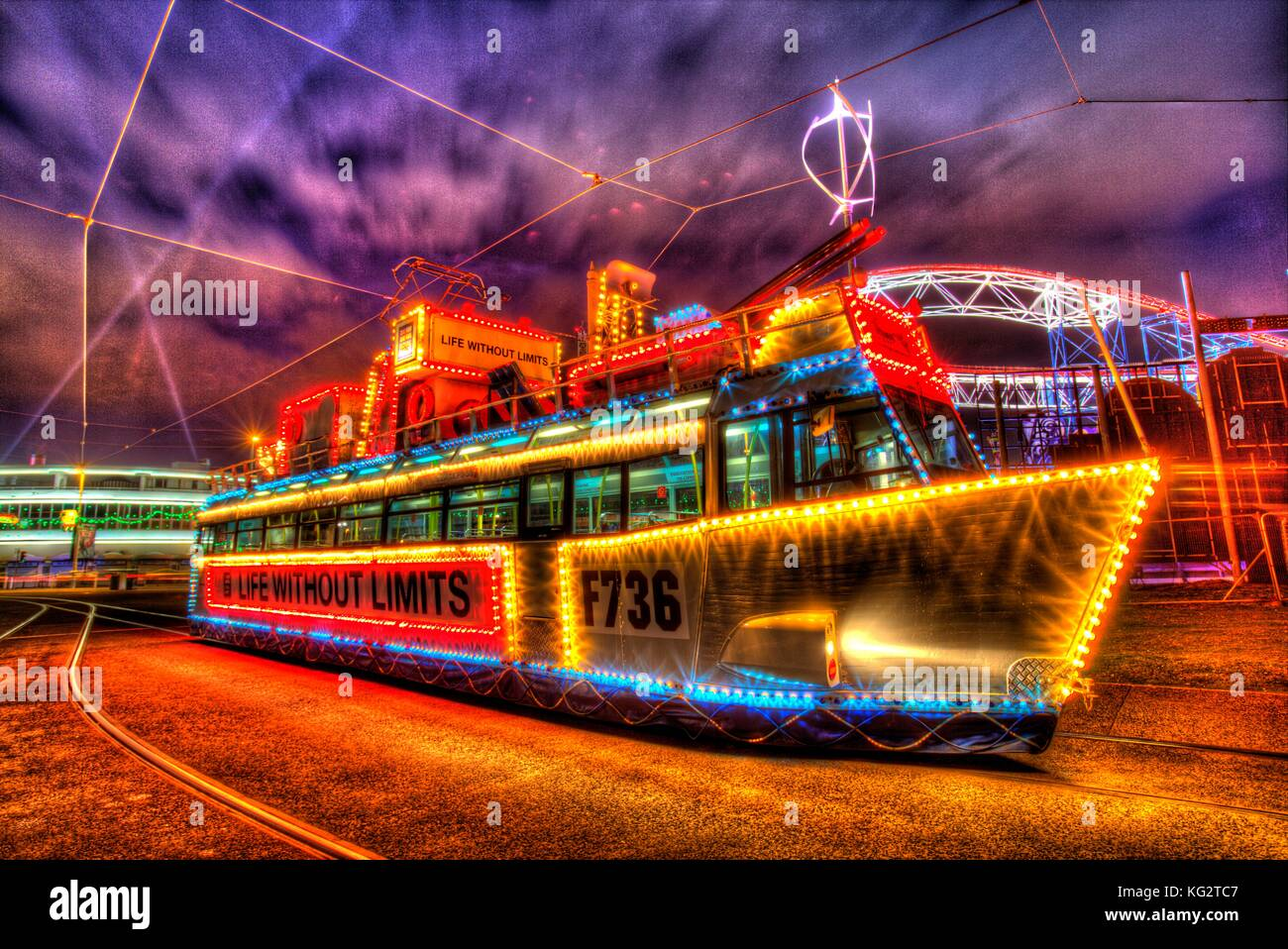 Town of Blackpool, England. Artistic night view of an illuminated tram dressed as a Royal Navy ship, during the Stock Photo