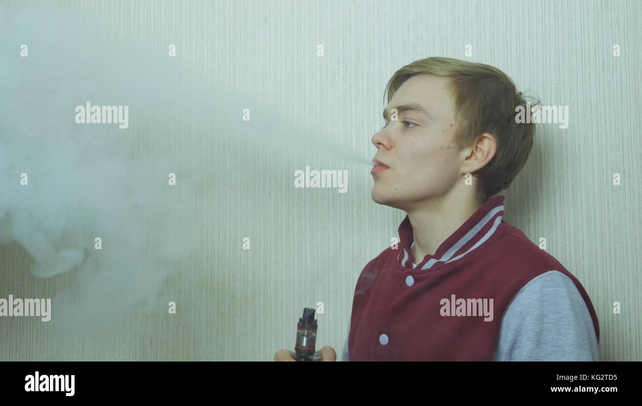 Young man vaping an electronic cigarette. Vaper hipster smoke vaporizer. Young man enjoying a satisfying e-cigarette - Stock Image