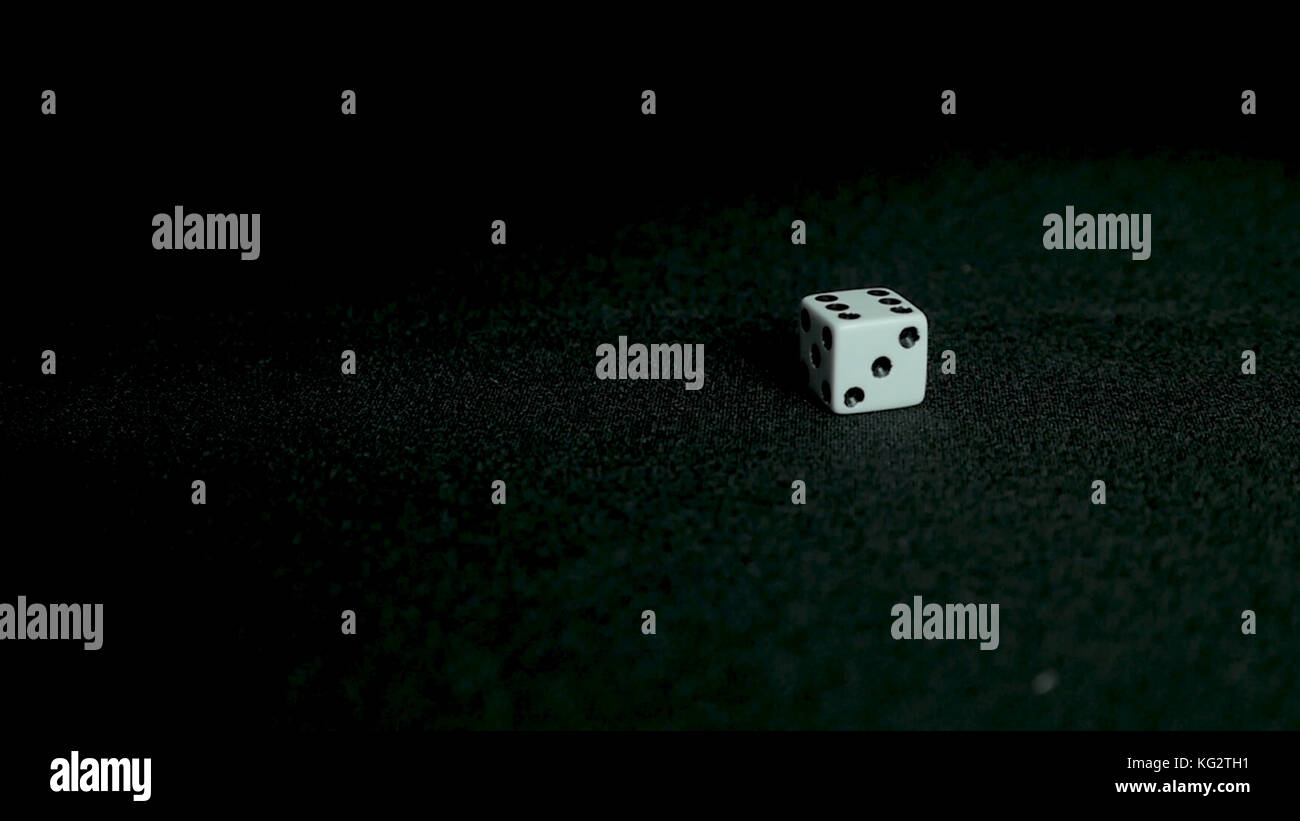 Female hand throwing dice on black background in slow motion. Two standard six-sided pipped dice with rounded corners - Stock Image