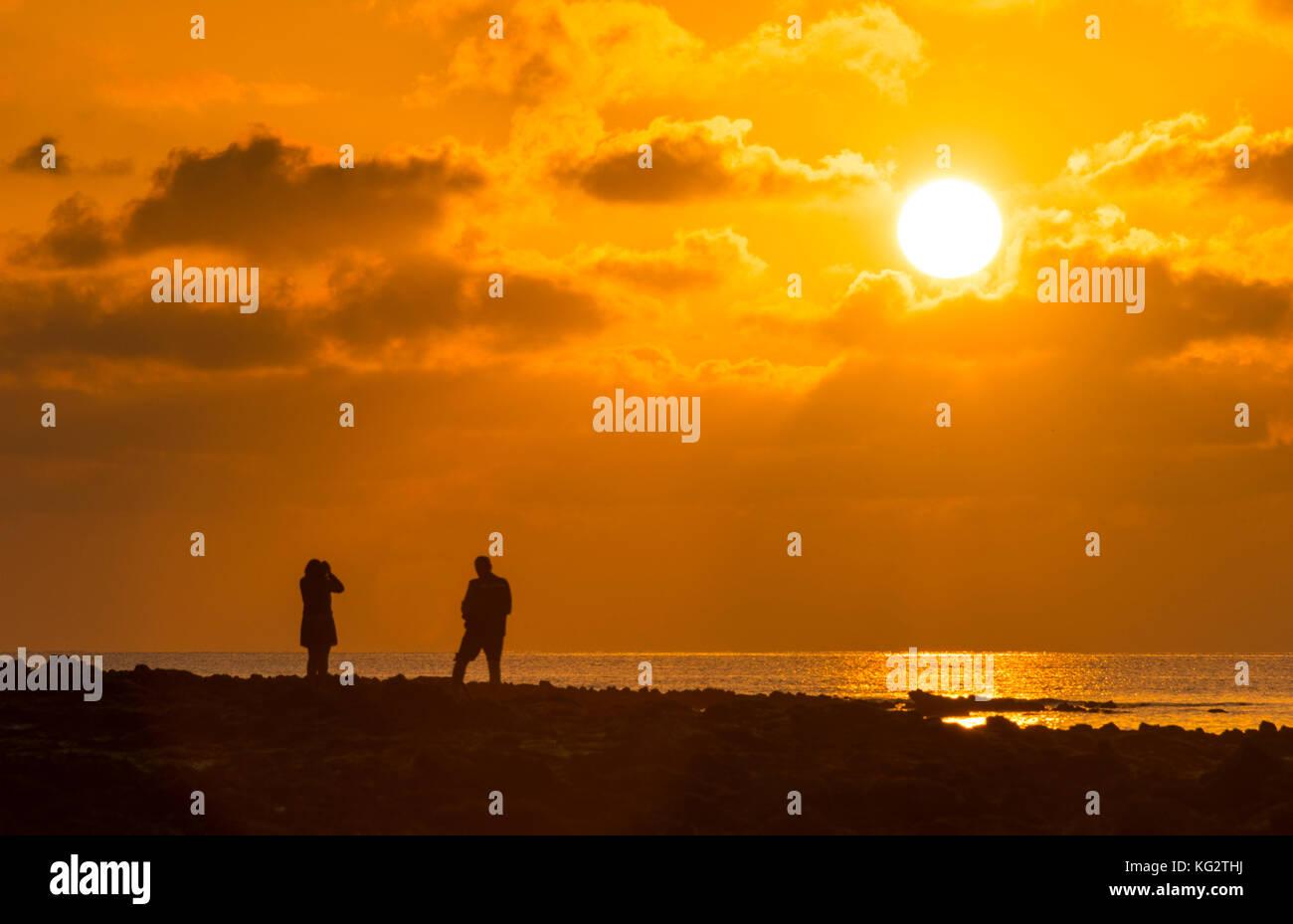 Silhouette figures admire sunrise at Arrecife, Lanzarote. - Stock Image