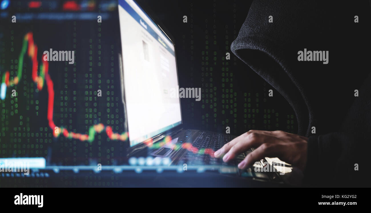 Internet crime and speculate stock concepts, Hacker working on computer laptop with downward stock graph background - Stock Image