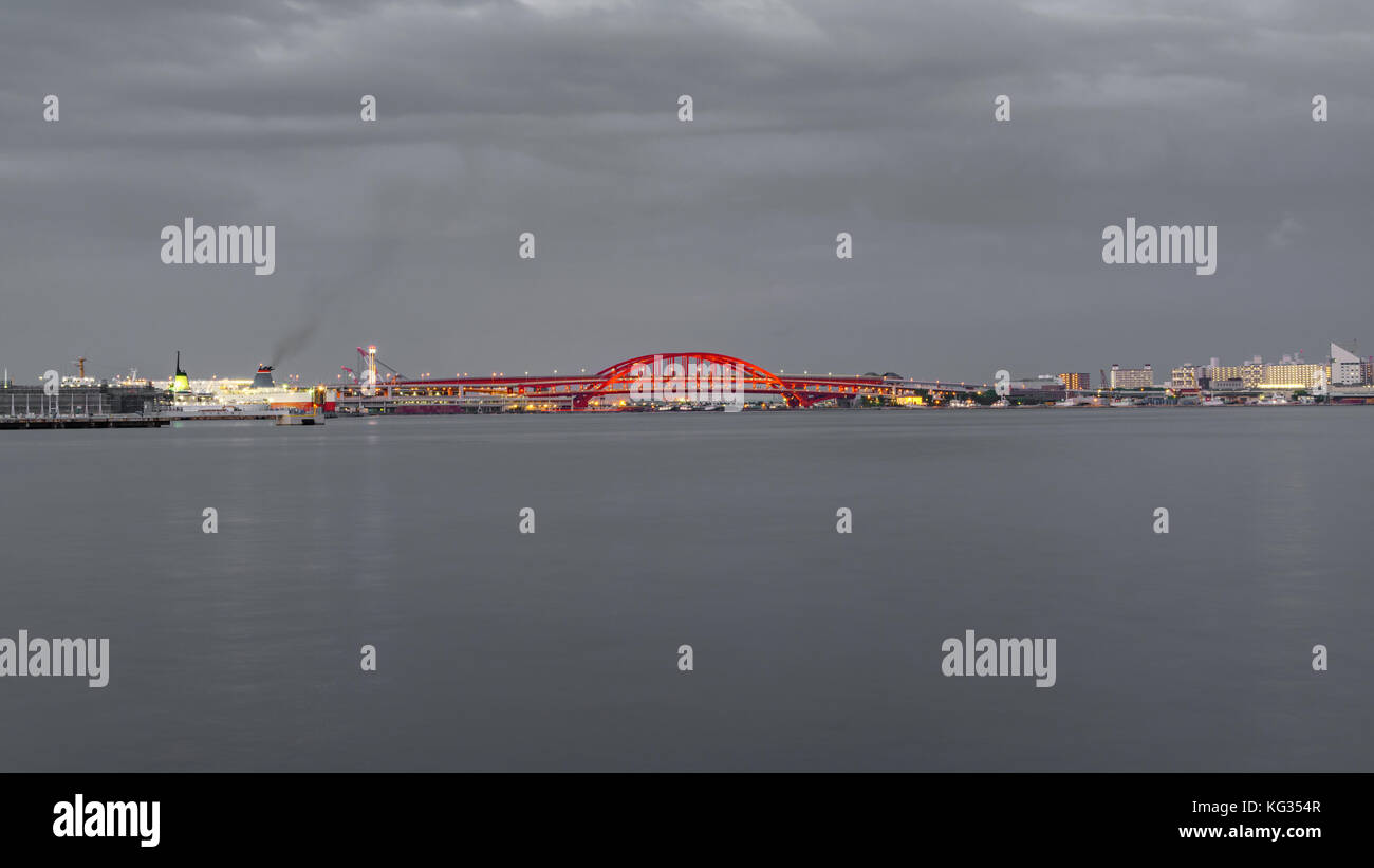 Red bridge, sea and city - Stock Image