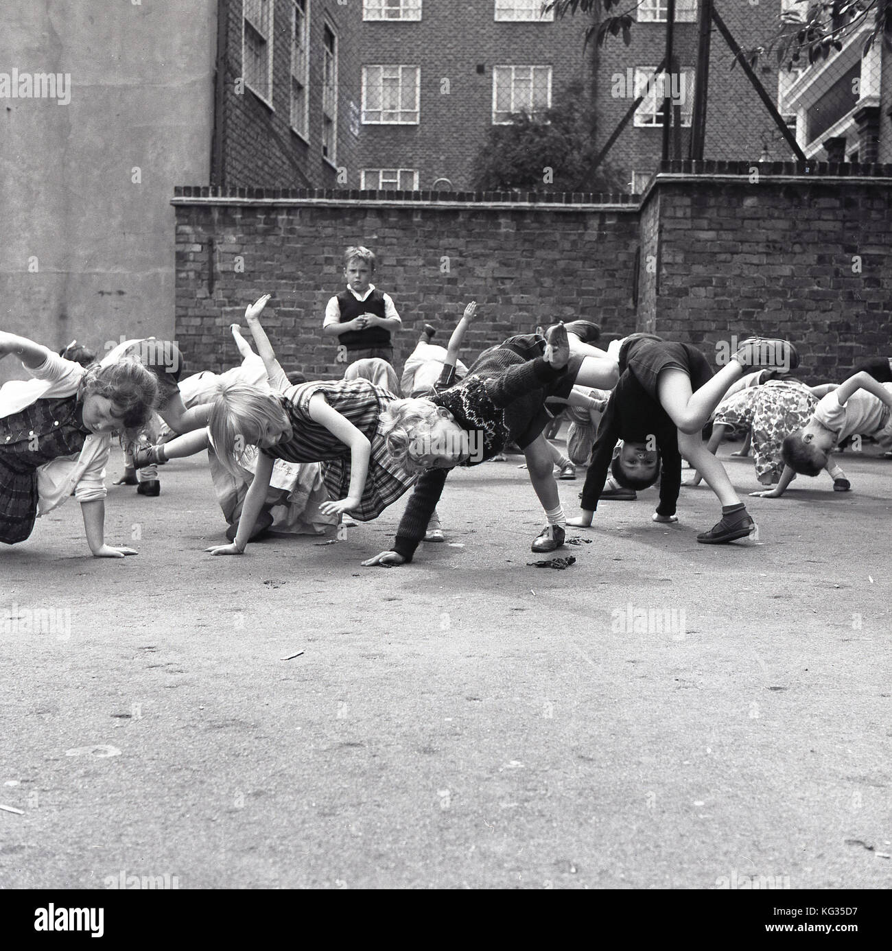 1960s, London, primary school children playing a game outside in the playground where they have to keep one hand - Stock Image