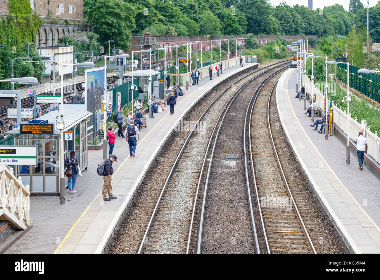 London, UK - October 23, 2017 - West Brompton overground station platforms, with commuters waiting on platforms - Stock Image