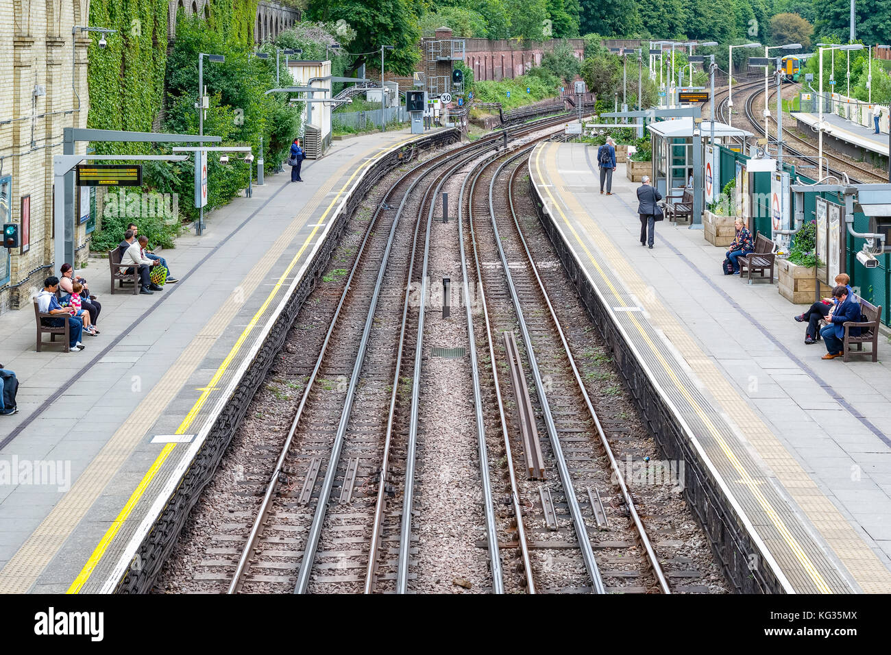 London, UK - October 23, 2017 - West Brompton underground station platforms, with commuters waiting on platforms - Stock Image