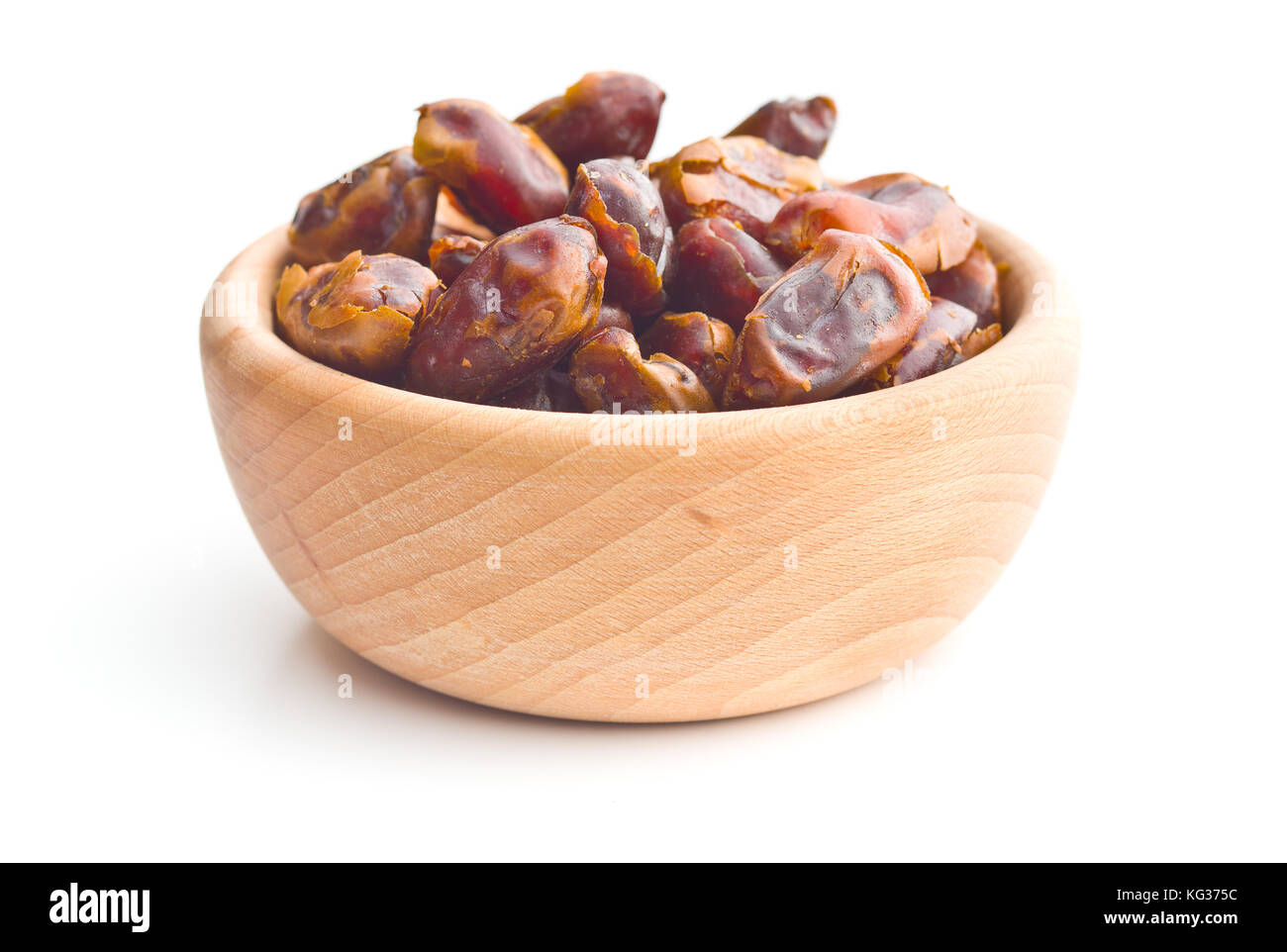 Sweet dates without stones in bowl isolated on white background. - Stock Image