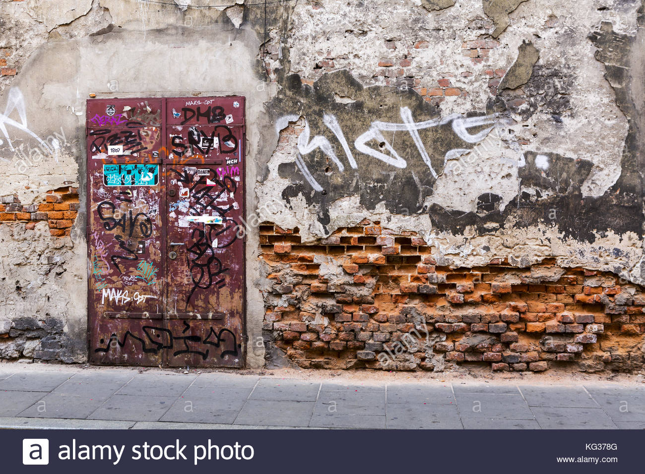 Poster and graffiti covered door in the wall of a building in Krakow which has been erroded by water splashed by - Stock Image