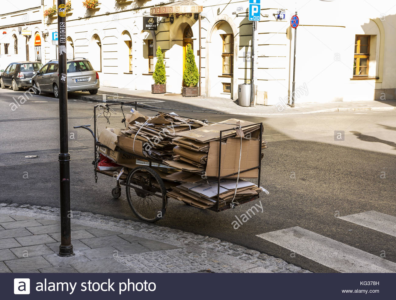 Old fashioned cart stacked with recyclable cardboard stood in a street in Krakow, Poland - Stock Image