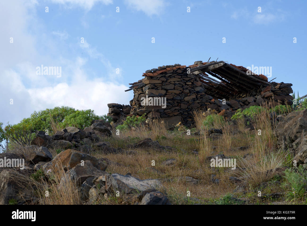 morbid house fallen into ruin on a hill under the blue sky - Stock Image