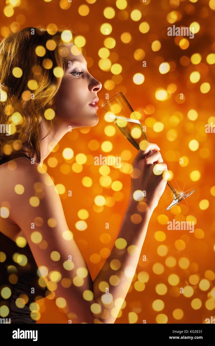 christmas theme, woman drinks a glass of sparkling wine on blurred bright lights background, banner template with Stock Photo