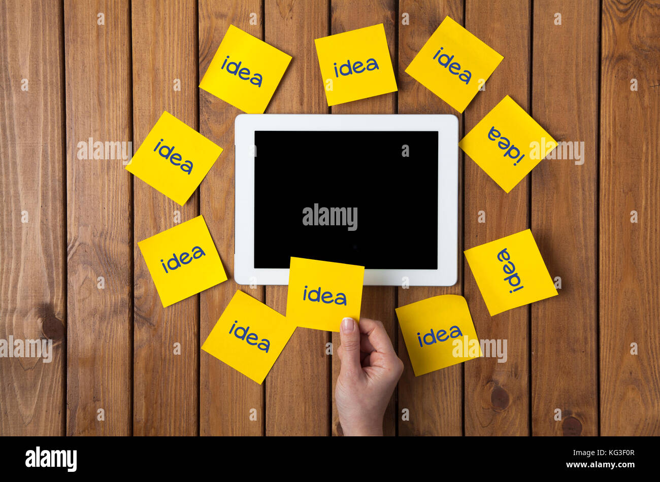 Businesswoman holding at word idea written sticky note and digital tablet. - Stock Image