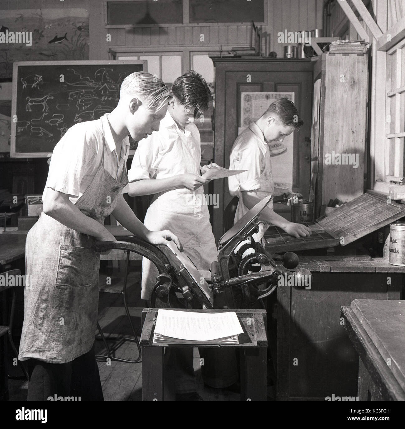 1950s, England, three young lads in white overalls using a printing press in a wooden workshop. - Stock Image