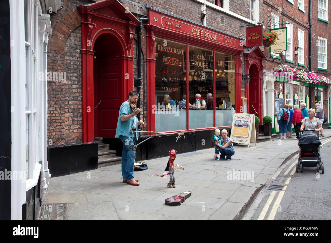 Street musician and puppeteer busking on Low Petergate Street,  York City, England - Stock Image