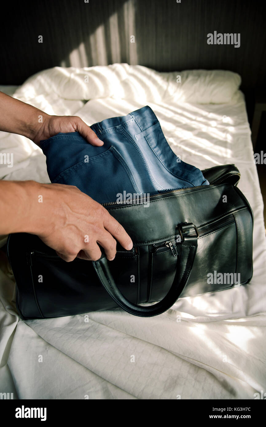 closeup of a young caucasian man putting clothes in a travel bag or putting them off, on the bed - Stock Image