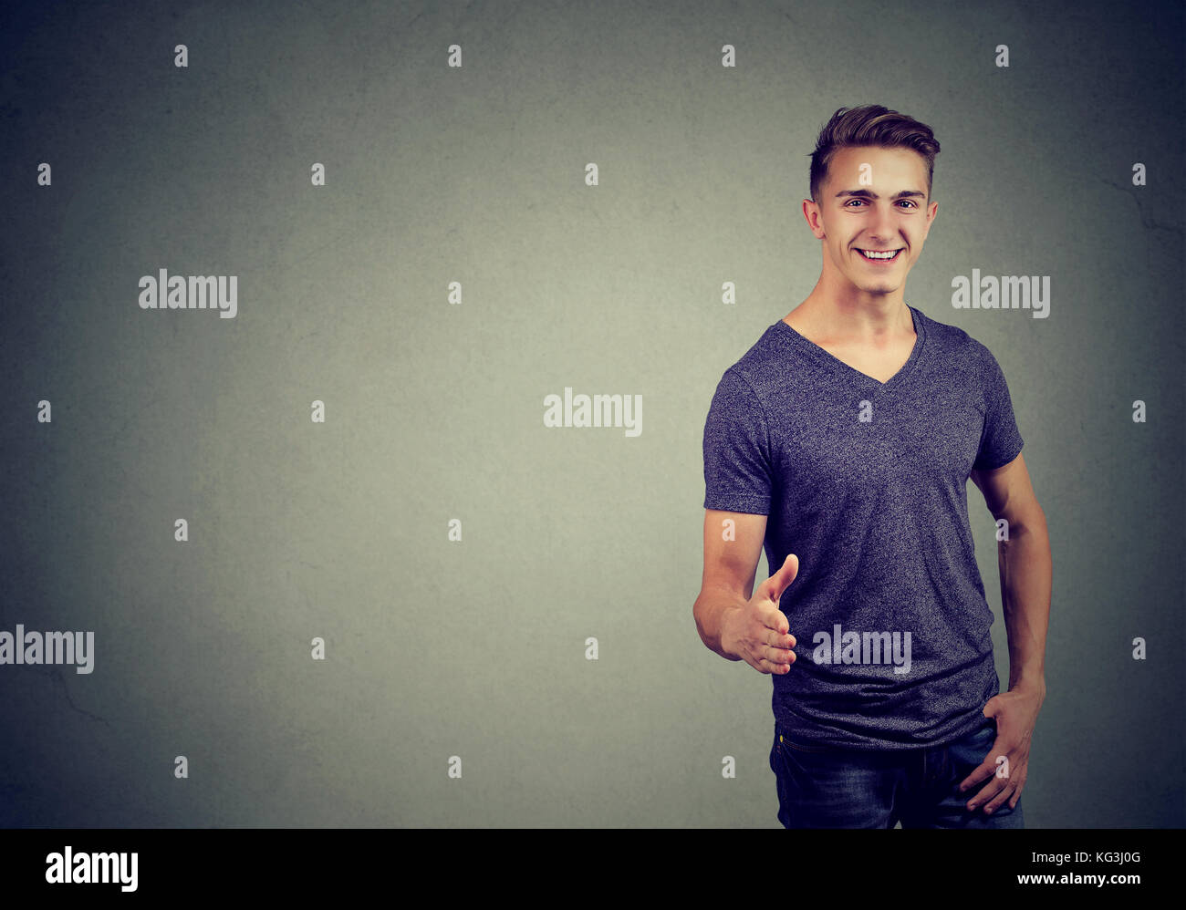 Smiling man in t-shirt holds out his hand for a handshake and looking at the camera over gray background - Stock Image