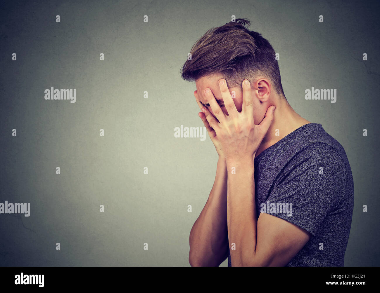 Side profile of a sad man with hands on face looking down. Depression and anxiety disorder concept Stock Photo