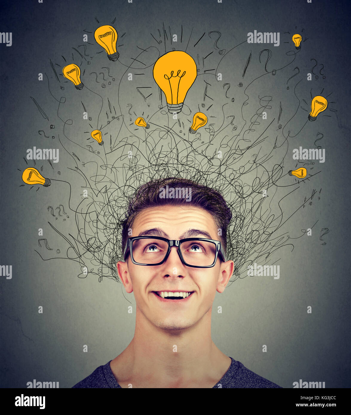 Brain connections. Excited man looking up at many ideas light bulbs above head isolated on gray wall background. - Stock Image
